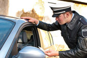 Police officer checking driving license — Stock Photo