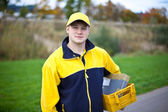 Young postman in a postman uniform — Stock Photo