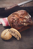 Black bread with a knife on a wooden table — Stock Photo
