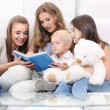 Mother Sitting With Children Reading Story - Stock Photo