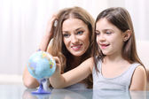Mother and daughter looking at a globe — Stock Photo