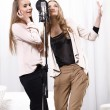 Two girls singing around the microphone in the studio — Stock Photo