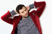 Handsome man posing in a red jacket — Stock Photo