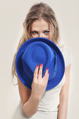Beautiful girl holding a blue hat — Stock Photo