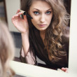 The young beautiful girl does makeup — Stock Photo
