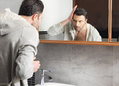 Young man looks at himself in the mirror — Stock Photo