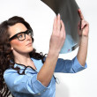 Female doctor looking at an X-ray sheet — Stock Photo #23563985