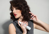 Beautiful girl laying fixes using hairspray — Stock Photo