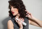 Beautiful girl laying fixes using hairspray — Stock Photo