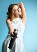 Beautiful girl in a white dress holding a bottle with hairspray — Stock Photo