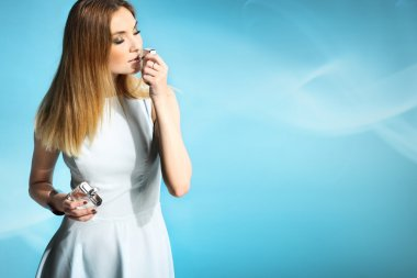 Beautiful girl in a white dress smelling perfume
