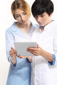 Two young doctors holding tablet pc in hands — Stock Photo