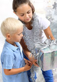 Sister gives her brother a Christmas gift — Stok fotoğraf