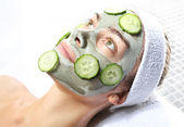 Relaxes in the mask with green clay and cucumber — Stock Photo