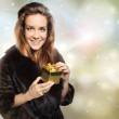 Elegant lady in a fur coat with a gold gift — Stock Photo #34889431
