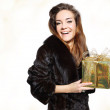 Happy lady in a fur coat with a gold gift — Stock Photo #34889639