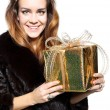 Lady in a fur coat with a gold gift — Stock Photo