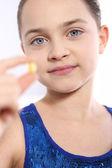 Caucasian girl holding a yellow pill — ストック写真