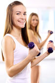 Training with weights, two young women in the gym — Stock Photo