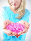 Female hands they keep colored crystals — Stock Photo