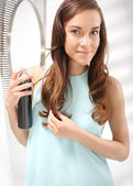 Woman brushing her hair, arranged curls, sprayed lacquer, — Stock Photo