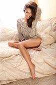 Alegre joven belleza sentada en el sofá luminoso y relajante — Foto de Stock