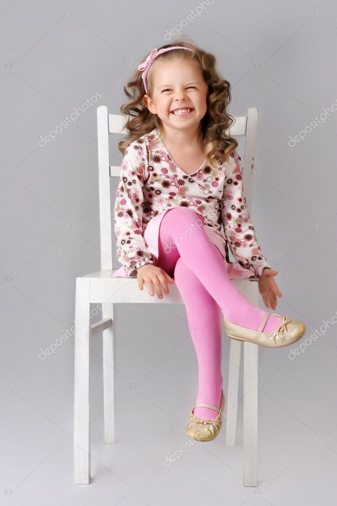 Cute Little Child Sitting On The Chair And Smiling Stock