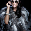 Pretty woman wearing sunglasses and beautiful fur — Stock Photo
