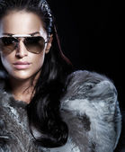 Portrait of brunette woman wearing sunglasses and beautiful fur — Stock Photo