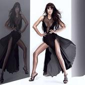 Fashionable young woman posing in long black dress — Stock Photo