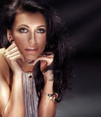 Portrait of brunette beauty in jewelry — Stock Photo
