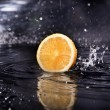 Slice of fresh lemon over the dark background with water — Stock Photo