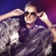 Fashionable photo of brunette young lady in sunglasses and fur — Stock Photo