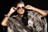 Beautiful brunette lady wearing fur and sunglasses. — Stock Photo
