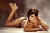 Sexy tanned brunette woman lying on the floor, naked. — Stock Photo