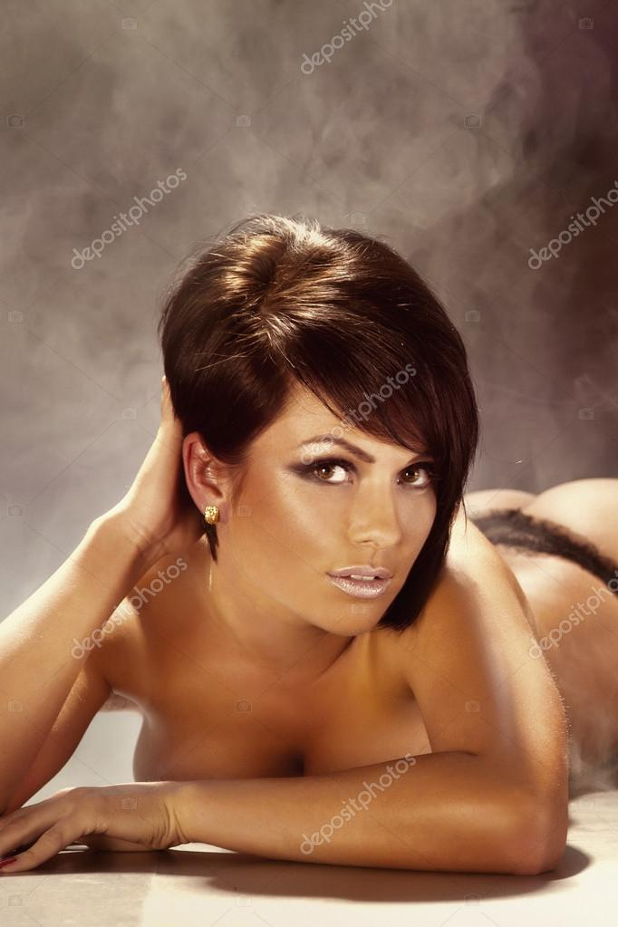 Sensual photo of beautiful sexy young brunette woman lying on the floor, looking at camera — Stock Photo #21074115
