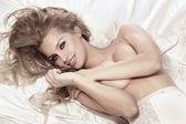 Portrait of smiling blonde woman lying in bed — Stock Photo