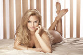 Sexy blonde woman lying naked on bed, looking at camera — Stock Photo