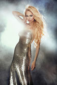 Portrait of cute blonde woman wearing silver fashionable dress. — Stock Photo