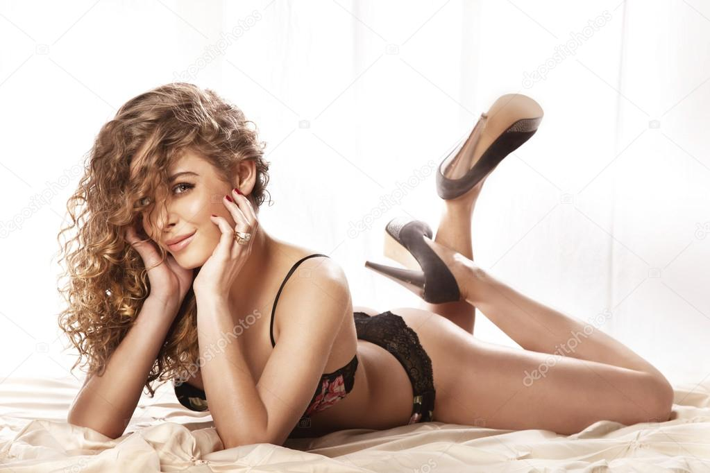 Happy Young Beautiful Woman With Long Curly Hair Lying In