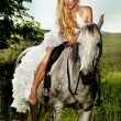 Young blonde bride riding a horse in fashionable dress. — Stock Photo