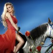 Beautiful blonde woman sitting on a horse in red dress. — Stock Photo #22919006