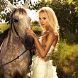 Beautiful blonde lady with posing with horse. — Stock Photo