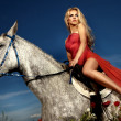Beautiful blonde woman sitting on a horse in red dress. - Stock Photo