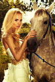 Portrait of gorgeous blonde girl with horse. — Stock Photo