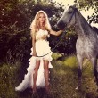 Beautiful young bride with horse in garden. — Стоковая фотография
