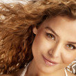 Stock Photo: Portrait of beautiful cheerful young womwith curly hair.