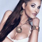 Portrait of beautiful brunette woman wearing gorgeous jewellery. — Stock Photo