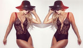 Sensual blond twins posing in black lingerie and hat. — Stock Photo