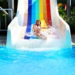 Little girl on a waterslide in aquapark. — Stock Photo #27561149